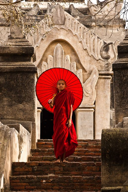 young monk with red umbrella
